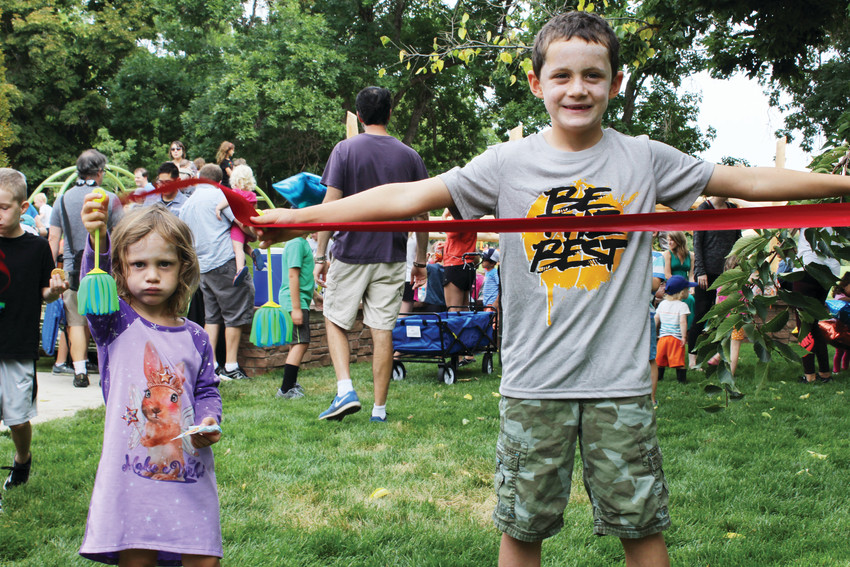 Ellington, left, and Samuel Lehr held up a piece of the ribbon from the opening of the new playground at Washington Park in August. The city is reaching out to community members to decide what will be done with the old playground space in the northern part of the park once it is decommissioned.