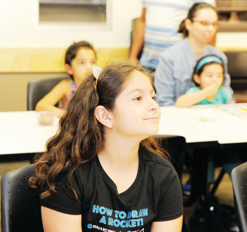 Alison Estrada, 10, listens intently as Loteria Maestra Michelle Hawkins explains the rules Aug. 28 at the Anythink Library York Street Branch.