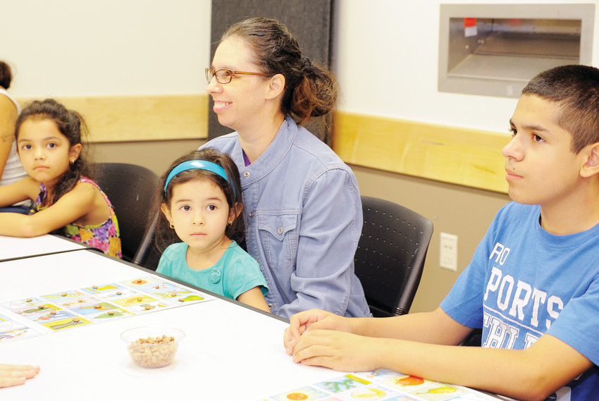 Teresa Valencia holds Esmeralda Garcia, 4, as they mark their loteria playing card with pinto beans Aug. 28 at the Anythink Library's York Street branch.
