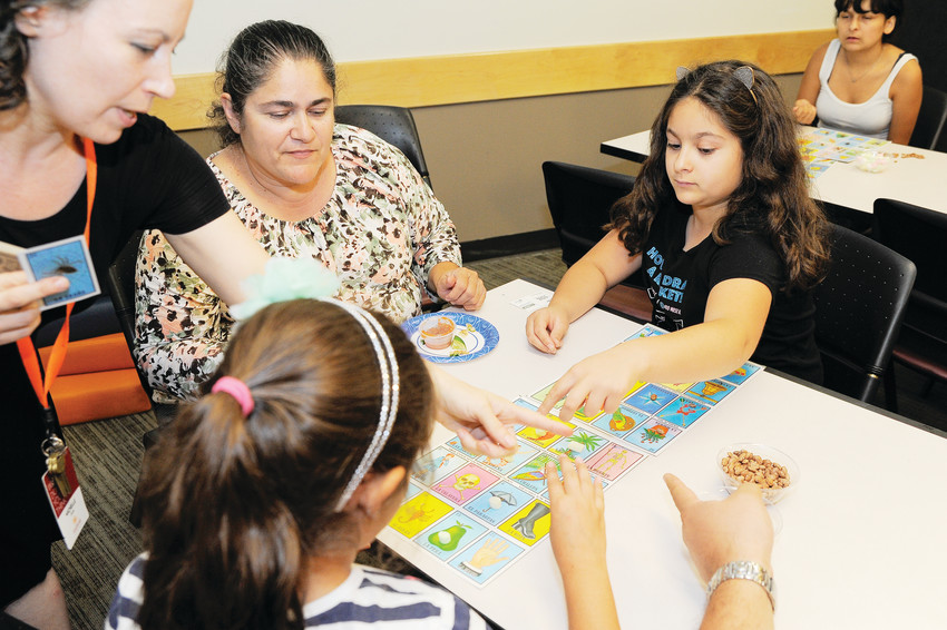 Anythink Library Guide Michelle Hawkins helps Alison Estrada, 10, and her sister Ivana, 7, mark their loteria cards Aug. 28 at the library's York Street branch.