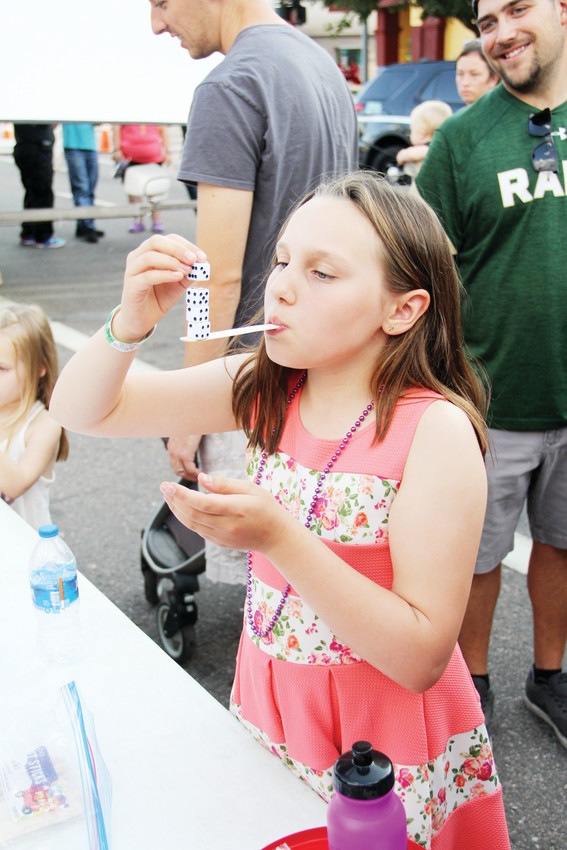 Sofia Boldt, 9, stacks dice on a small stick to see how many she can hold up at the Englewood Block Party Sept. 8. Volunteers led kids in several games in which they could win a prize.