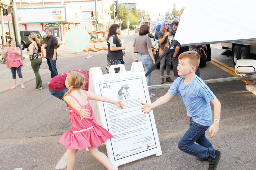 On left, Teagan Wille, 8, and Cayden Wille, 10, chase a balloon while playing one of the children's games at the Englewood Block Party Sept. 8. Volunteers led kids in several games in which they could win a prize.