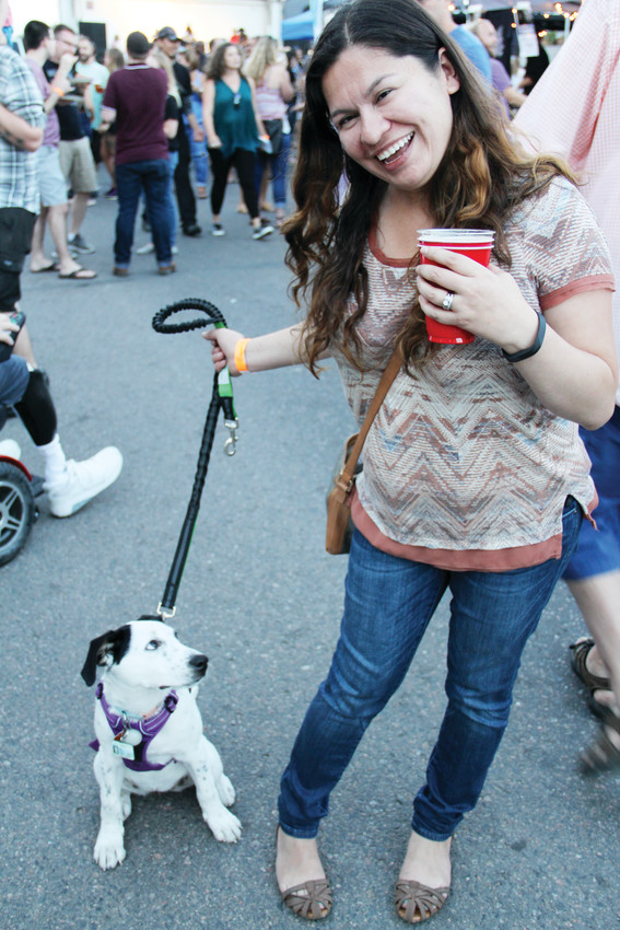 "Liz Rivera, 35, stands with her 4-month-old puppy, Posie, at the Englewood Block Party Sept. 8. ""She loves it,"" Rivera said. Several dogs were part of the crowd at the event."