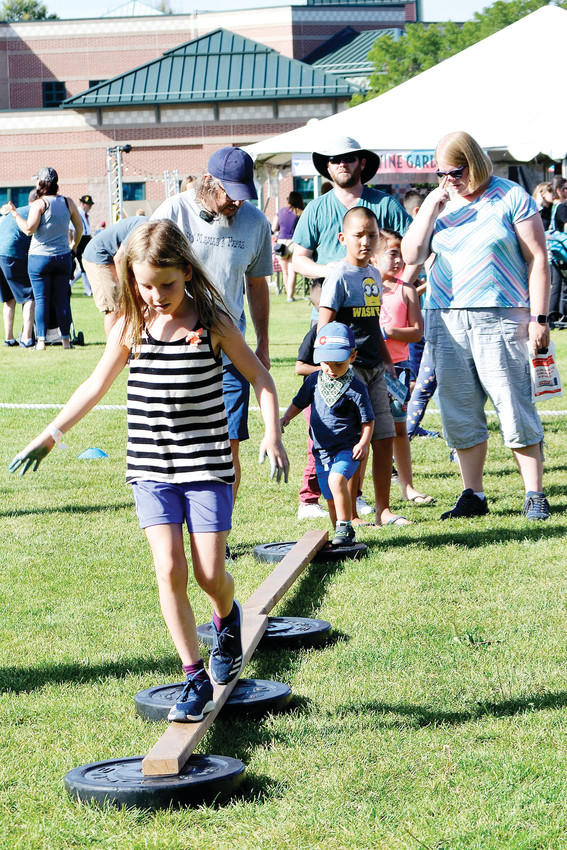 Cora Studeny, 9, of Wheat Ridge, completes a balance beam on an children's obstacle course during Ridge Fest on Saturday, Sept. 8. Her father, Mike, guides Hyde, 3, immediately behind Cora.