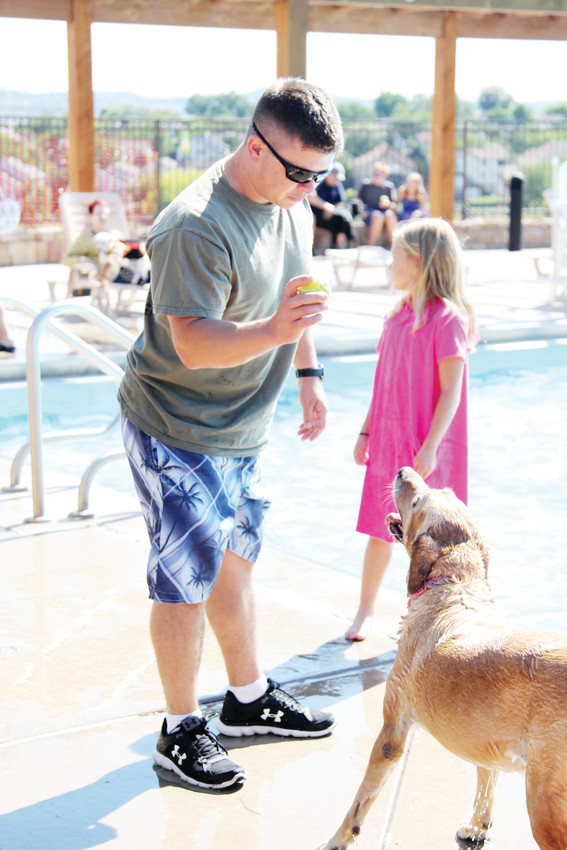 Mike Brumbaugh plays fetch with his yellow lab, Lilly, at the Pooch Plunge in Castle Rock on Sept. 8.