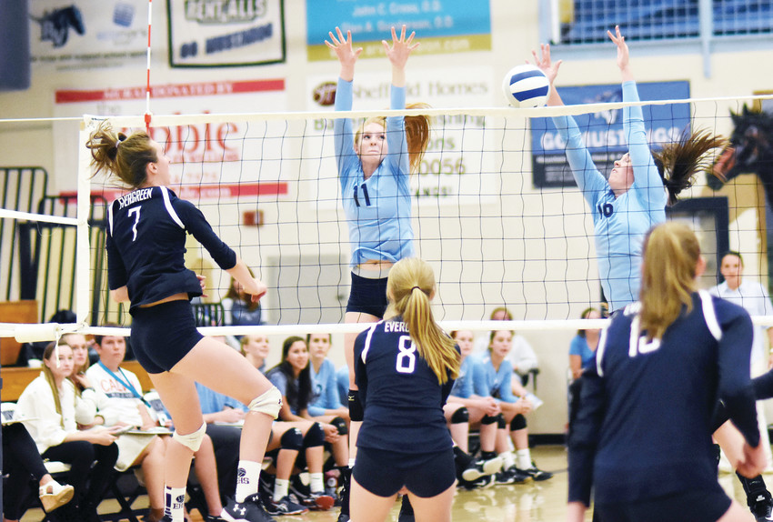 Ralston Valley's Natasha Eberle (11) and Jamie Dorczuk (16) attempt to block the spike attempt by Evergreen junior Gabby Clark (7) during a non-league game Sept. 6 at Ralston Valley High School. The Mustangs took a first-set victory, but eventually fell to the Cougars 3-1.