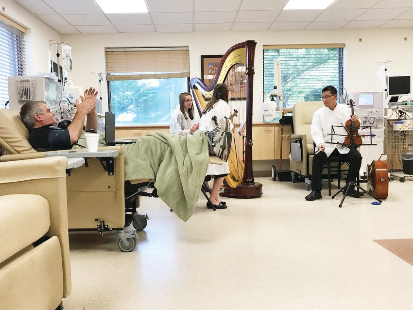 Marty Brauer applauds the Trainor siblings after their final song at the DaVita Kidney Care dialysis center. The trio played a 30-minute set to break up the monotony of going through dialysis treatment.