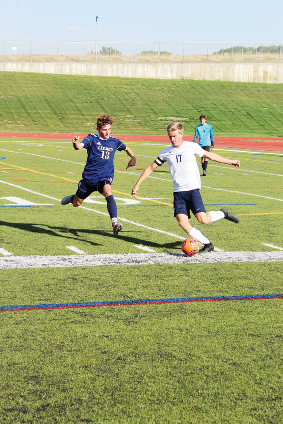 Ralston Valley senior Ben Johnson kicks the ball away from Legacy junior Hunter Hance at North Stadium Sept. 4.