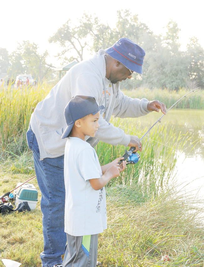 Michael Stitt of Thornton helps his grandson, Kawhi Patton, 5, with his line, during the Fishing Derby of this year's Thornton Harvest Fest at Grandview Ponds, Sept. 8.