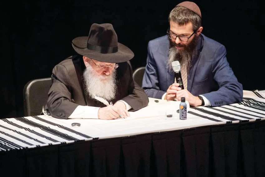 Rabbi Nissan Mangel puts the first strokes down on a new Torah at a Holocaust event in September 2017 at the Arvada Center. Workers in Israel have been working to complete the new Torah, which will be dedicated Sept. 16 at Westminster's College Hill Library.