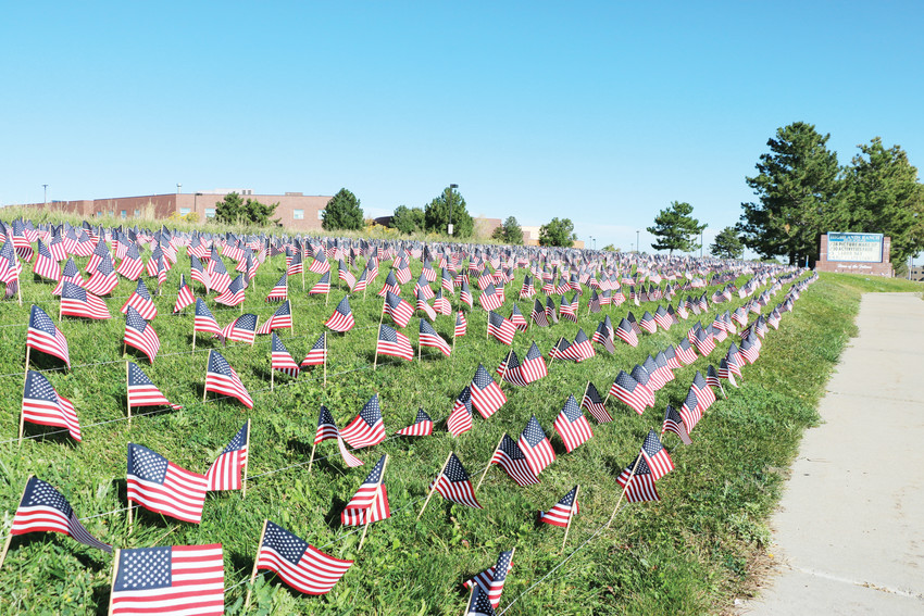 Highlands Ranch High School students place 2,977 American flags on a lawn near the high school, at the corner of University Boulevard and Cresthill Lane, to represent the lives lost on 9/11.
