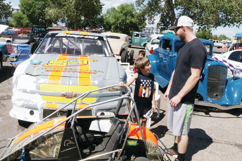 Matt Burton and his 6-year-old son Kale talk about racing. Matt drives the race car behind them and his son drives the quarter-midget race car parked in front of Matt's car.
