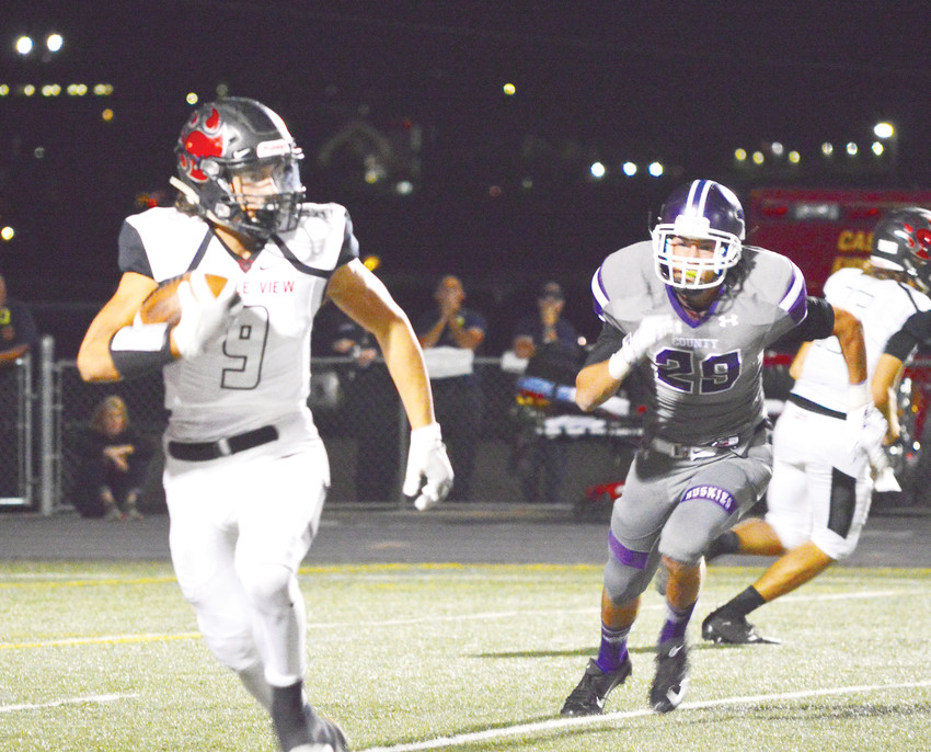 Castle View senior running back Jake Hribar heads toward the corner with a Douglas County defender in pursuit during the Sept. 14 game at Douglas County Stadium. Castle View notched its fourth straight victory over the Huskies with a 28-0 shutout.