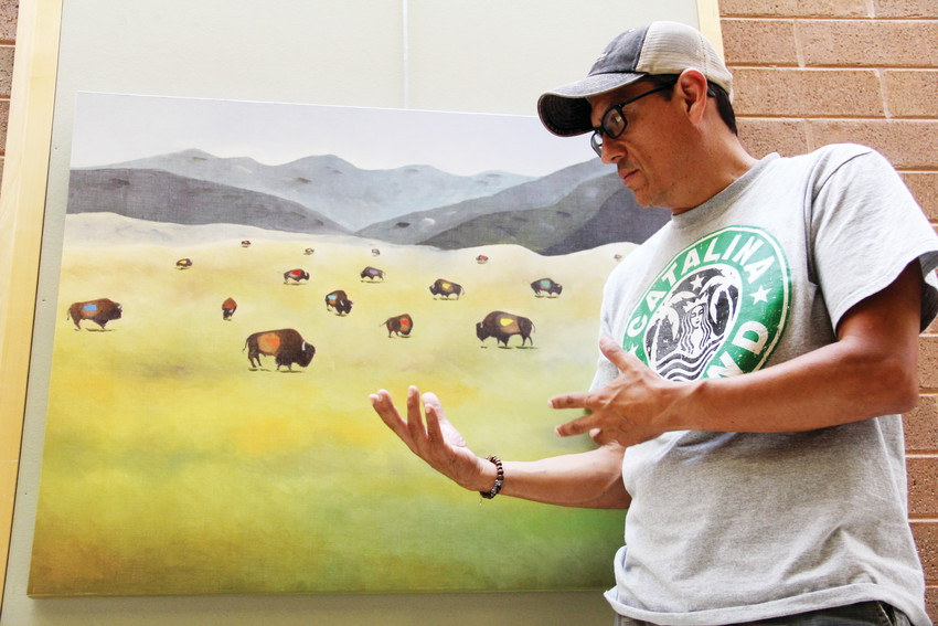 "Arturo Garcia, an artist from the Littleton area, talks about his painting, ""Where the Buffalo Roam,"" on display Sept. 13 at Goodson Recreation Center in Centennial. Garcia's work has been featured at several locations in the south metro area."