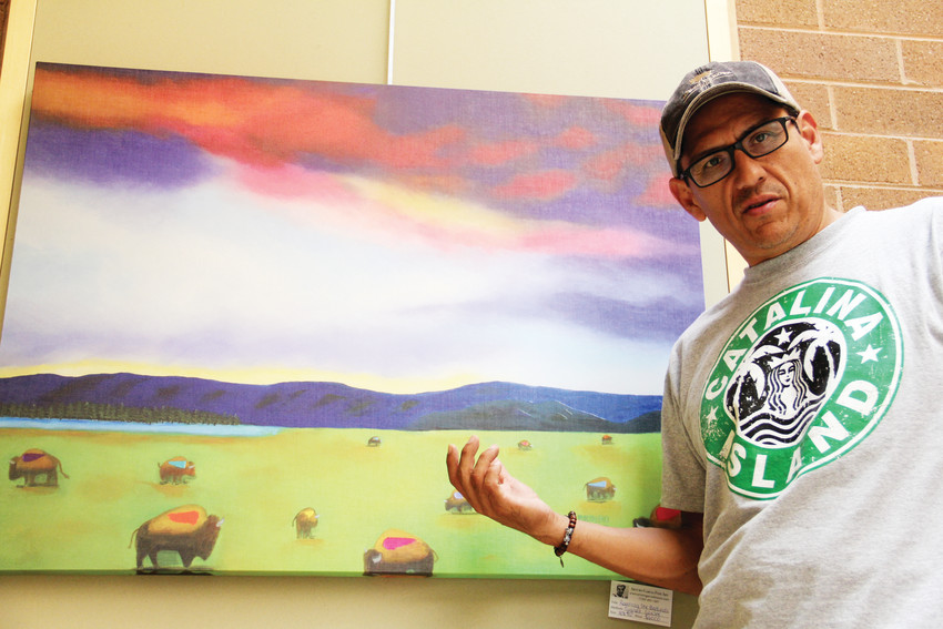 "Arturo Garcia, an artist from the Littleton area, talks about his painting, ""Roaming the Badlands,"" on display Sept. 13 at Goodson Recreation Center in Centennial. Garcia's work has been featured at several locations in the south metro area."