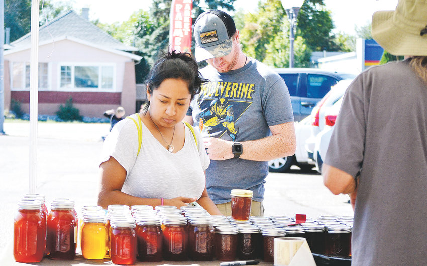 Annie and Doug Vetter, of Thornton, check out honey from Jeff Curry's booth at the Colorado Honey Festival in Wheat Ridge on Saturday, Sept. 22.