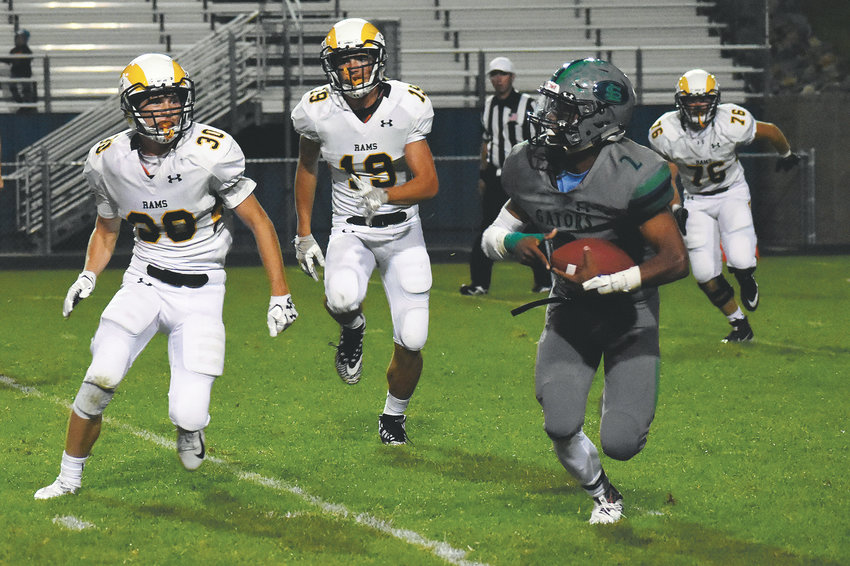 Green Mountain's Brad Golgart (30) and Will Banks (19) chase after Standley Lake quarterback Alex France on Sept. 21 at the North Area Athletic Complex.