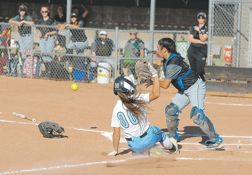 Mountain Range's Montanna Alley (00), scores her team's first run, as Monarch catcher Trish Leins awaits the throw during a Sept. 20 game at Mountain Range High School in Westminster. The Lady Mustangs scored score 6 more times to beat the Coyotes, 7-2.