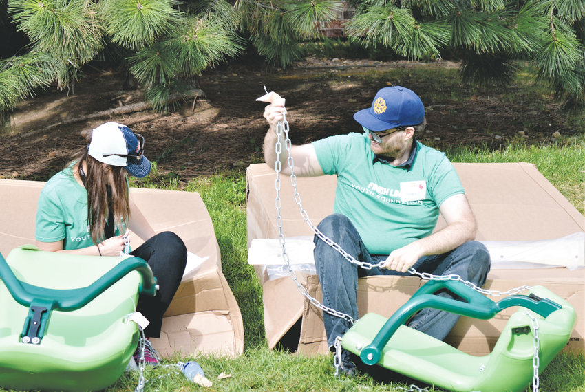 Unison Housing Community Manager Ashley Manz and Assistant Community Manager Nathan Earl try to puzzle together a swing set Sept. 20 at Thornton's Creekside Place. More than 200 volunteers came to the apartment complex to help build the playground and other features.