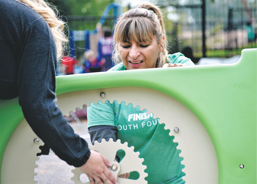 Unison Assistant Manager Gloria Esbejo and Holly Asbach of Finish Line Youth Foundation work to assemble the gears on a playground toy for the new play area at Thornton's Creekside Apartment Complex Sept. 20.