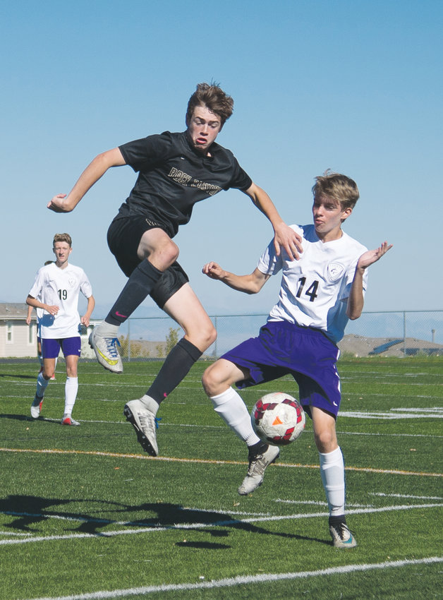 Rock Canyon's Jack Tibbett, left, and Douglas County's Cameron Travis get some air going for the loose ball.  The Jaguars defeated the Huskies 3-0 at Rock Canyon on Sept. 22.