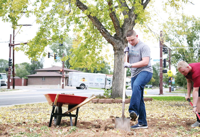 "Joel Parks works with fellow students on yardwork for an Arvada homeowner. ""We're leading by example by doing this,"" Parks said."