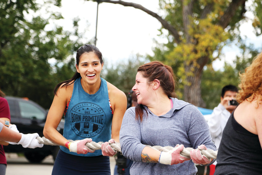Andrea Nale celebrates with her teammates from Arvada CrossFit after completing the fire truck pull Sept. 29.