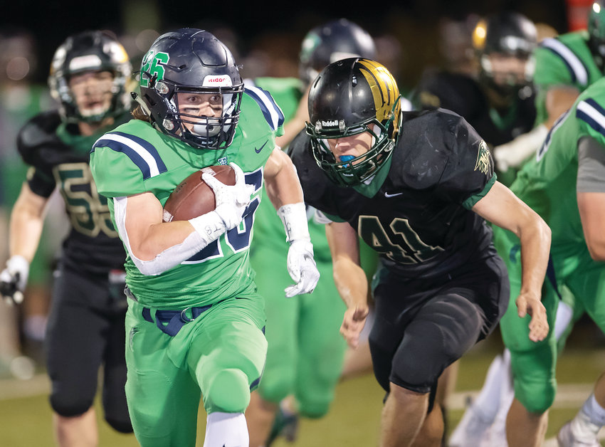 ThunderRidge's Spencer Lambert rumbles for some of his 173 yards on the ground as he's chased by Mountain Vista's Christopher Perella (41).  Lambert's Grizzlies cruised to a 49-10 victory at Shea Stadium on Sept. 28.