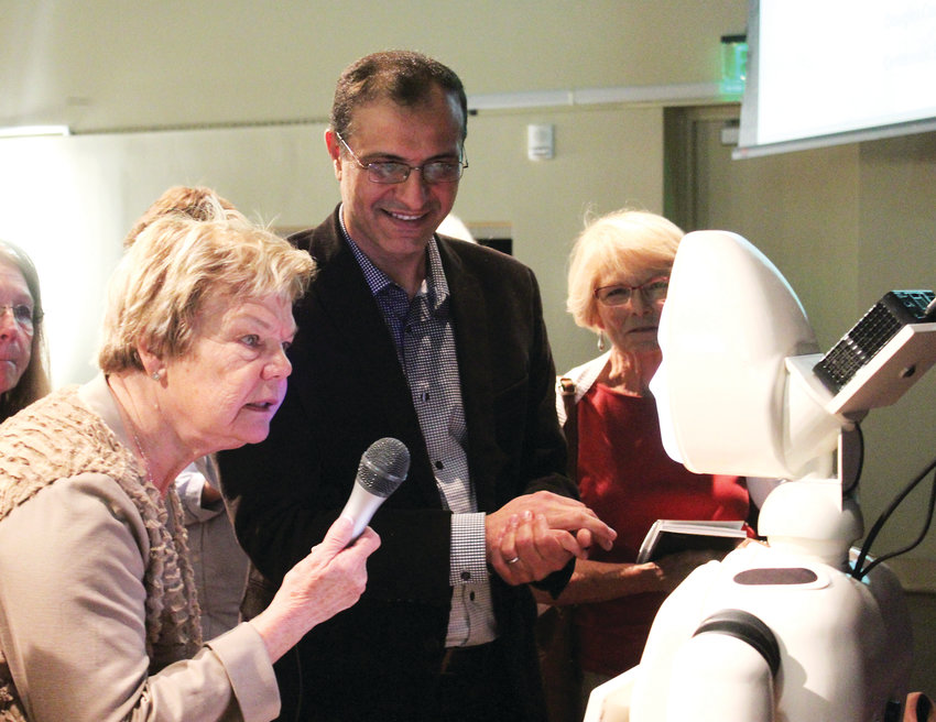 Carol Rossi, 81, tests out Ryan, an artificial intelligence robot designed to help dementia patients by being a social companion, at the Living and Aging Well Seminar at the Lone Tree Arts Center Sept. 29. The robot was developed by a group of University of Denver researchers, led by associate professor Mohammad Mahoor, pictured.