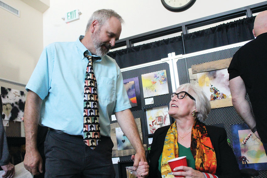 Mark Hollenbeck holds Sandra Esparza's hand at the art show of completed works from Lutheran High School students, who portrayed their own style on unfinished pieces of her late husband, Henry, a Denver artist and teacher.