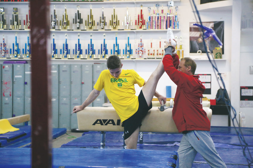 Taylor Burkhart stretches with his coach, Vladimir Artemev at a morning session at 5280 Gymnastics.