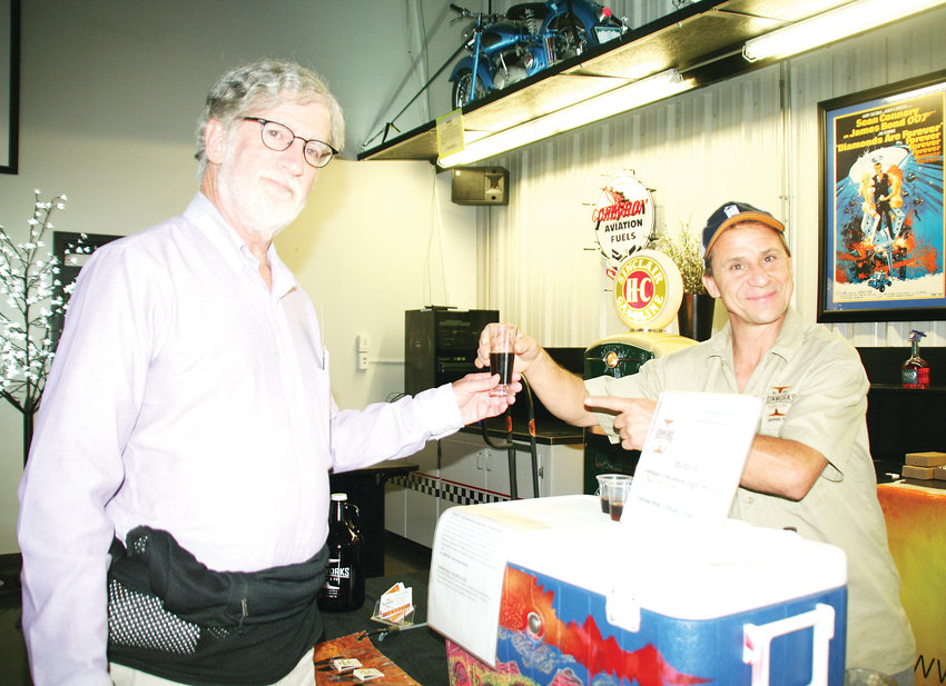 Scott Davis, left, a member of the Jefferson County Library Foundation, receives a sample of the Horchata Porter from Wade Maslen, the head brewer at Ironworks Brewery & Pub in Lakewood, during the Jefferson County Library Foundation's event.