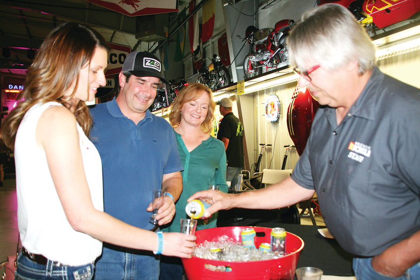 Rick Abitbol, right, the head brewer who along with his wife Jaqua owns Brewery Rickoli in Wheat Ridge, pours a beer for Arvada resident Sarah Jacobs as her husband Rick and friend Lisa Padgett watches. Sarah Jacobs is the branding sponsor for the Stouts & Stories, Ales and Tales fundraiser.
