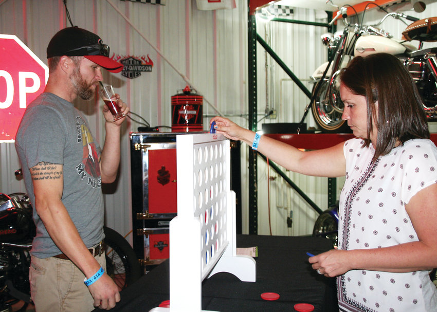 David Farr and Jess Labudda of Arvada play a giant connect four game during the Jefferson County Library Foundation's Stouts & Stories, Ales and Tales kick-off party Sept. 27 at the Lamar Street Center in Arvada.