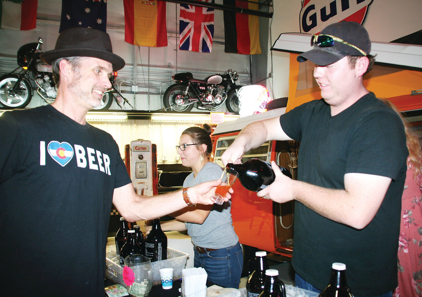 Michael Sutherland, a beer tender at Grand Lake Brewing in Olde Town Arvada, pours a Vienna Style Lager for Ed McIlvain of Golden during the Jefferson County Library Foundation's Stouts & Stories, Ales and Tales kick-off party Sept. 27 at the Lamar Street Center in Arvada.