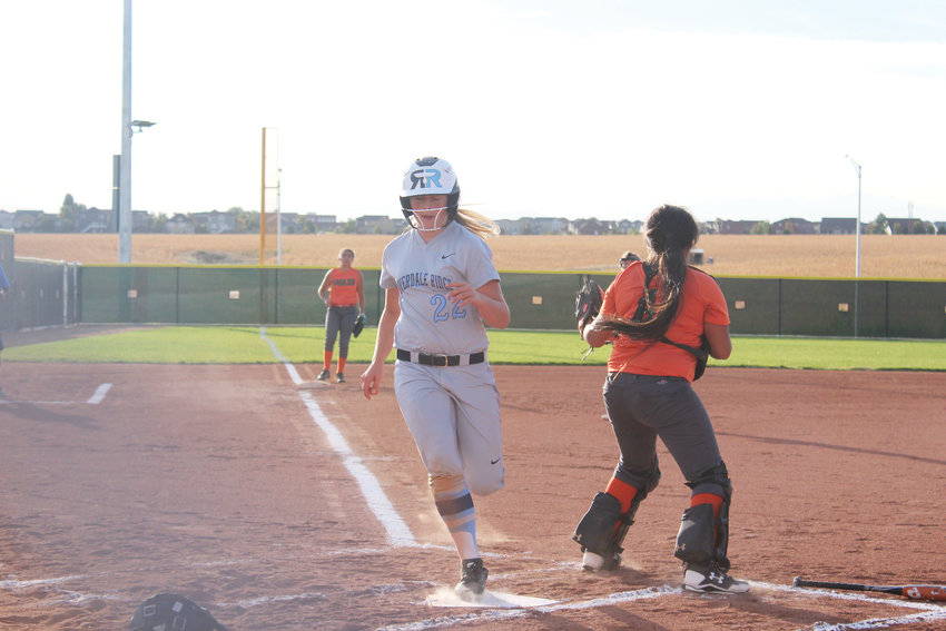 Lady Ravens' freshman Gianna Benallo scores  the team's first run in Game 1 of the double- header against Adams City on Sept. 26.
