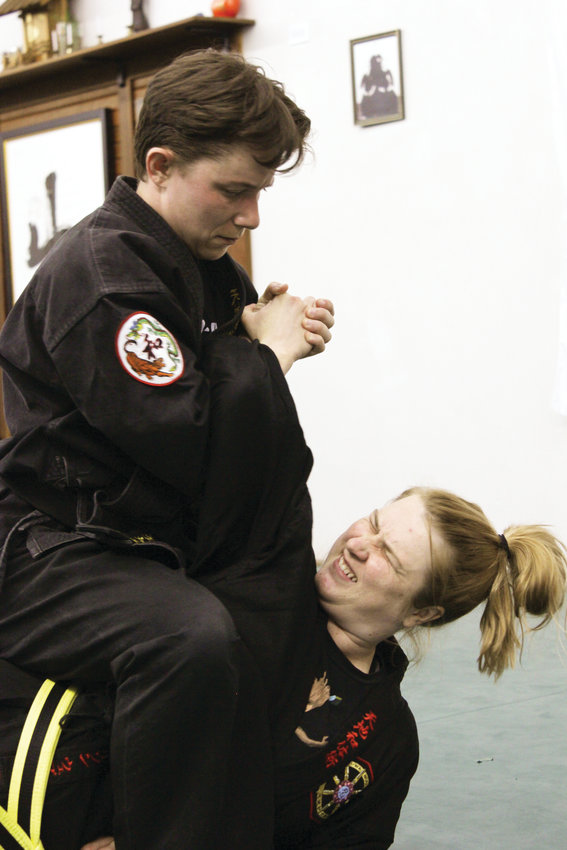 Vanessa Spindle, a teacher at Wash Park Martial Arts, shows Allison Webster how to use a particular take down. Spindle has been doing martial arts since she was a child.