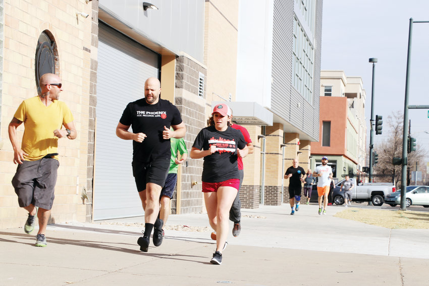 Members of The Phoenix gym participate in a run in the Five Points neighborhood. The Phoenix help people in recovery from addiction build a support community through fitness.