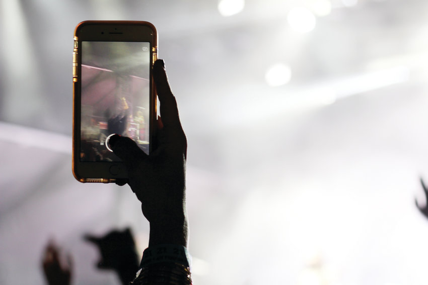 An audience member takes a photo of the Young the Giant performance on Saturday evening. The festival was held at the Overland Park Golf Course in south Denver.