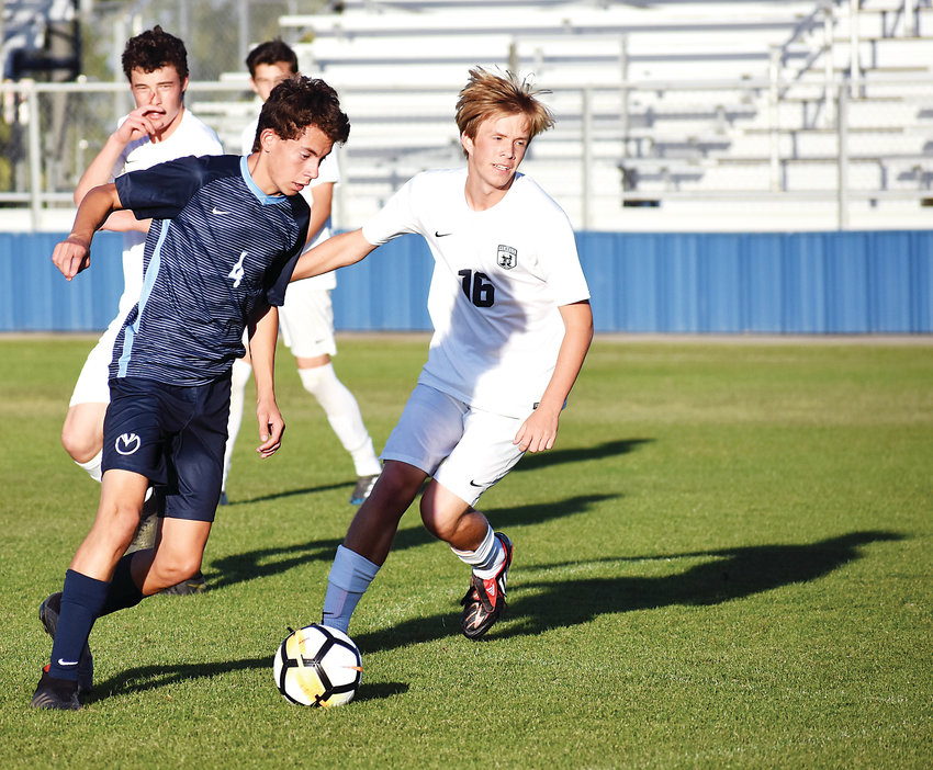 Ralston Valley senior Cort Johnson (4) drives toward the net as Columbine senior Connor Watz (16) tries to cut off Johnson's path Sept. 27 at the North Area Athletic Complex in Arvada. Ralston Valley won 3-1.