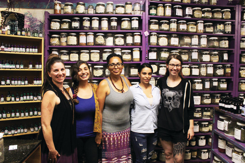 Kaewyn Picard, left, and several of her staff members stand in the herbs section of the Herbs and Arts store on Colfax Avenue. Herbs and Arts sells oils, herbs and crystals for spiritual healing.