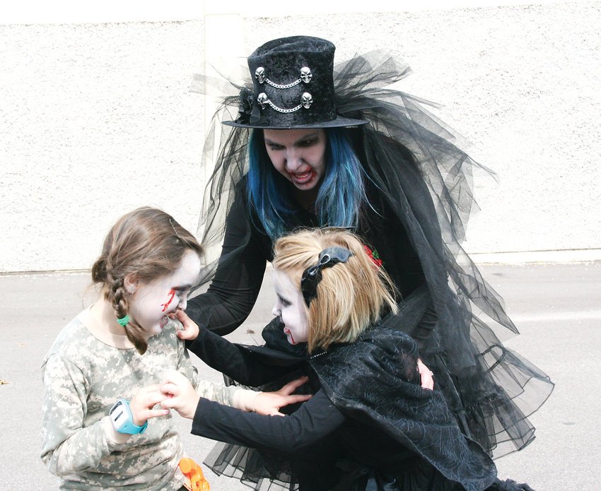 Jill Raynor and her daughter Jema, 7, play with Jema's friend Shelby Whitley, 7, all of Littleton during the Littleton Zombie Crawl and Pig Roast on Oct. 6.