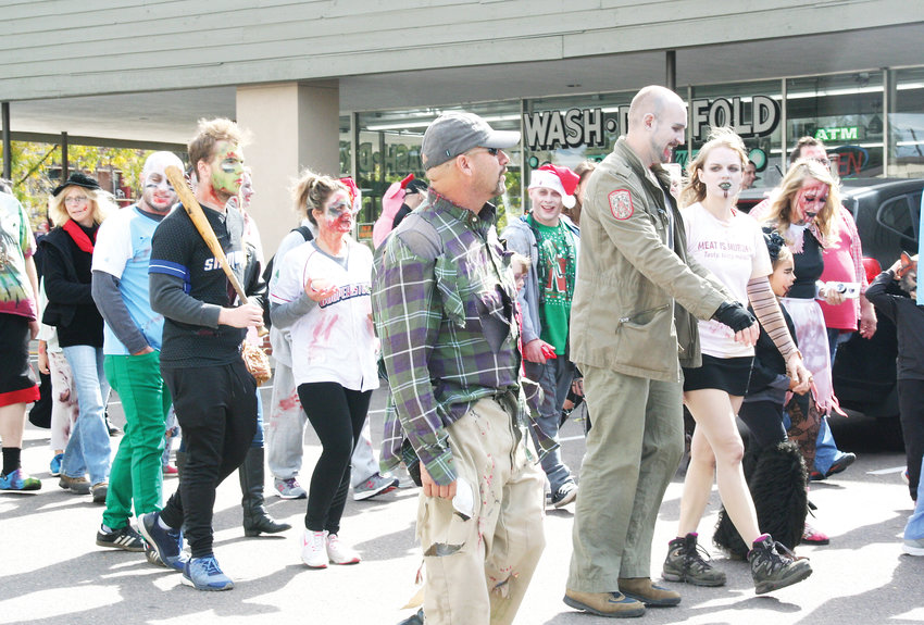 A group of zombies leave the Woodlawn Shopping Center for their travel west to Reinke Brothers for a free pig roast meal during the Littleton Zombie Crawl and Pig Roast on Oct. 6.