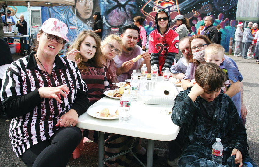 A group of family and friends of Littleton enjoy the pig roast, served up by the Littleton Elks Lodge 1650, following the zombie crawl on Oct. 6 in downtown Littleton.