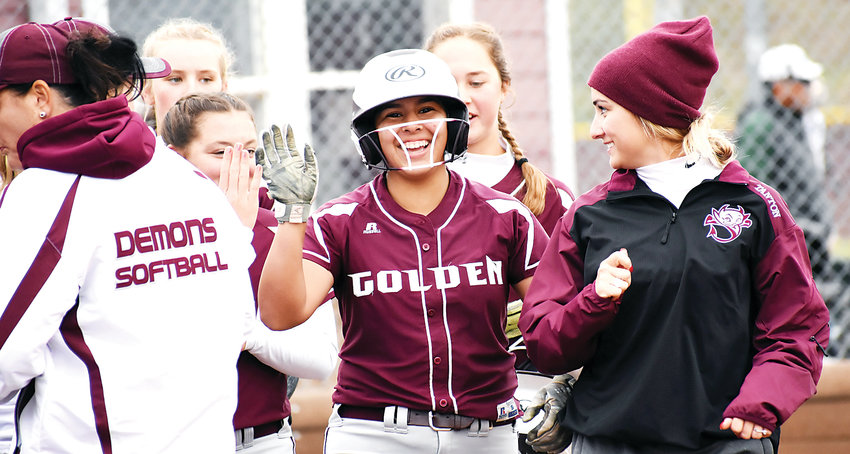 Golden senior Jade Gomez, middle, is congratulated by teammates and coaches after her 2-run home run in the bottom of the first inning against D'Evelyn on Oct. 6. It was Gomez's first home run of the season. The Demons won 17-1 to win Golden's first softball conference title since 1995.