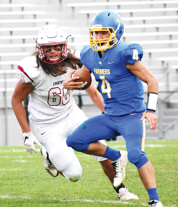 Wheat Ridge senior quarterback Anthony Tate (4) scrambles for yardage while being chased down by Chatfield senior Anthony Johnston on Oct. 4 at Jeffco Stadium. The Farmers suffered a 29-28 loss in their Class 4A Jeffco League opener.
