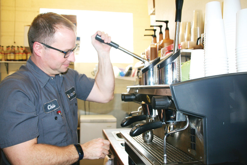 Chris Smith, the service advisor at Lube & Latte in Lakewood, makes a latte on Oct. 4. The business opened in 2007 and offers Denver's Novo Coffee and Sugar Bakeshop pastries.