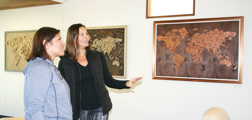 Golden artist Charlotte Bassin gives a guided tour of the art gallery at Canyon Point to Jackie Berz of Denver. Bassin's Wander and Wonder World Maps are on display at Dr. Amy Shearer's Canyon Point Orthodontics and Dr. Paul Madlock's Canyon Point Implant and Oral Surgery in Golden.