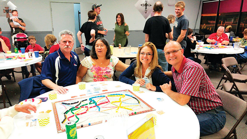 Seated at the table from left, Tom and June Schichtel and Rob and Wendy Semin, try out some board games during the September 2016 Friends and Family Game Night, hosted by Jo Ellen and Kevin Christian of Centennial. The Christians will be opening their new business, Game Train, in Highlands Ranch in December.