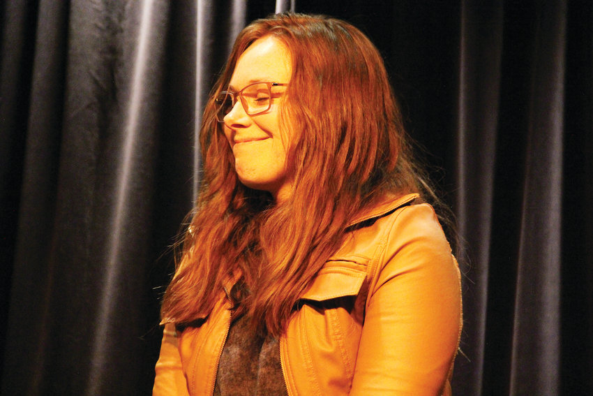 Elizabeth Frances, 27, smiles on stage Oct. 3 at The Forum Theater in Koelbel Library in Centennial. She performed, singing harmony, with her husband at the library's songwriter showcase.